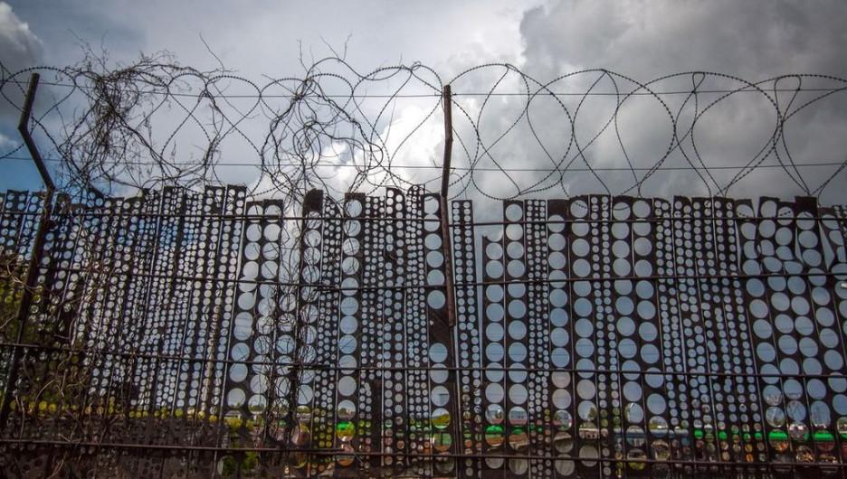 Забор с колючей проволокой.