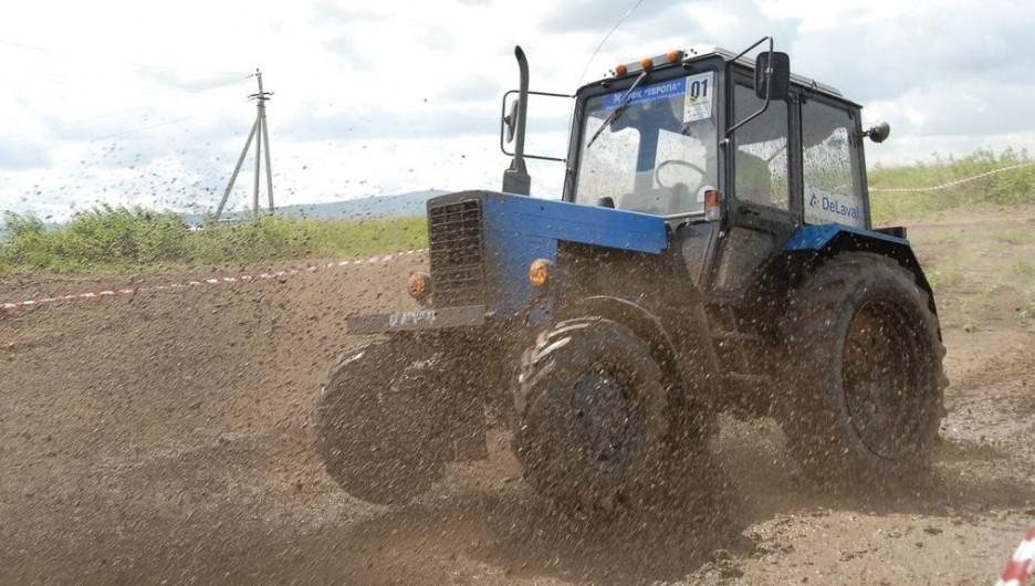 Трактор мчит по грязи.