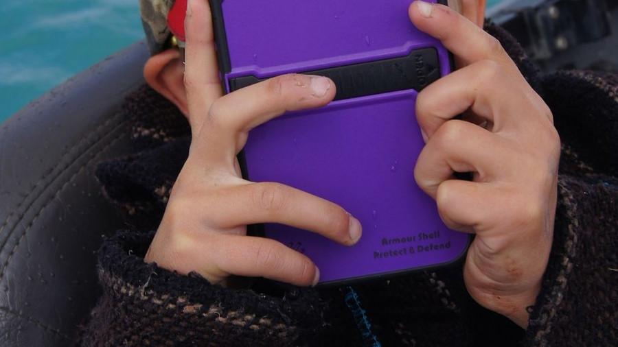 Мобильный телефон в руках у ребенка.