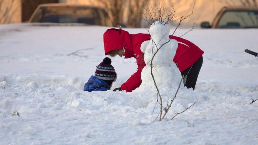 Мама и ребенок лепят снеговика.