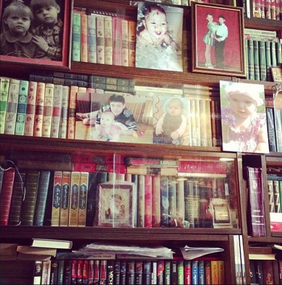 Домашняя библиотека на полках за стеклом