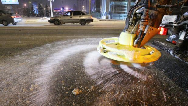 Обработка дороги песчано-соляной смесью.