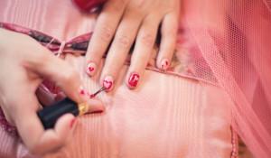 Девушка красит ногти.