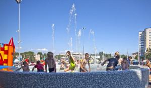 Жара, дети купаются в фонтане.