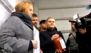 """Активисты принесли банку с надписью """"Кровь детей Донбасса""""."""