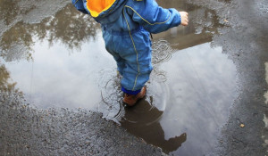 Ребенок шагает по луже.
