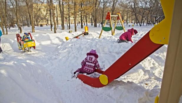 Дети играют в снегу на детской площадке.