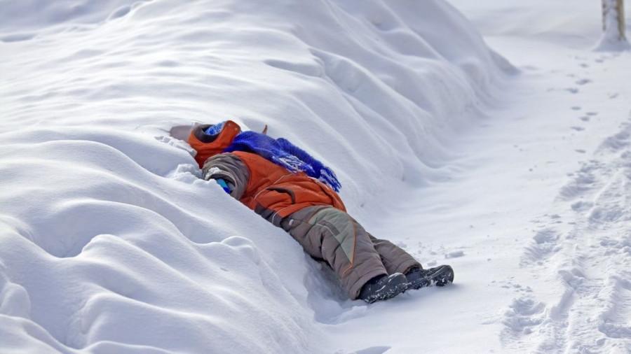 Много снега. Ребенок играет.