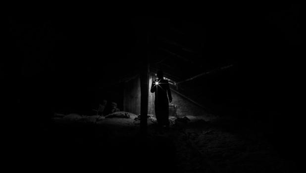 Мужчина с фонариком в темноте.