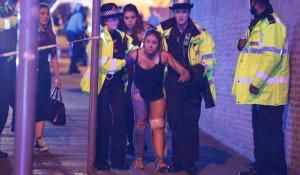Полицейские ведут пострадавшую от взрыва на стадионе Манчестера. 22 мая 2017 года