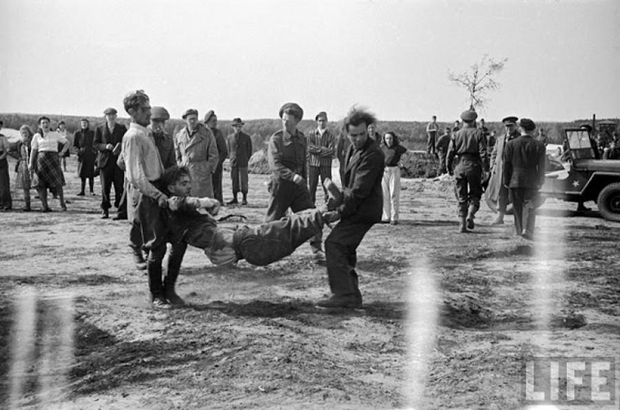 Солдаты СС несут другого солдата, потерявшего сознание от обилия трупов.