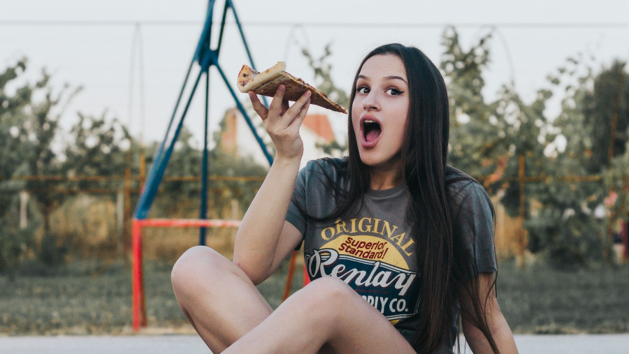 Школьница ест пиццу.