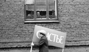 Владимир Соколаев. Женщина с плакатом спешит на первомайскую демонстрацию. Новокузнецк. 1983.
