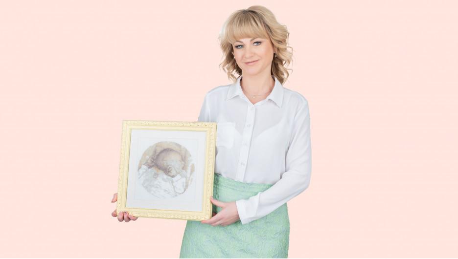 Наталья Воронова, ведущий репродуктолог «Клиники Пасман» с картиной, которую ей подарила пациентка — эту вышивку она сделала 10 лет назад и дала зарок подарить ее доктору, который сможет помочь ей родить ребёнка.