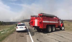 Пожарные борются с возгоранием сухой травы.