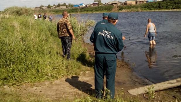 На берегу реки ищут утонувших детей.