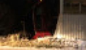 Красный автомобиль протаранил забор и врезался в жилой дом.
