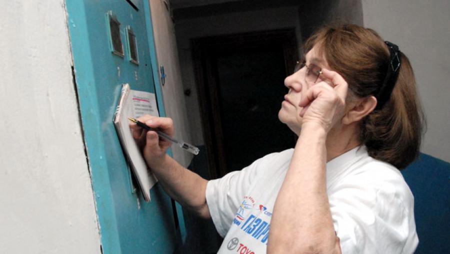 Женщина снимает показания счетчика.